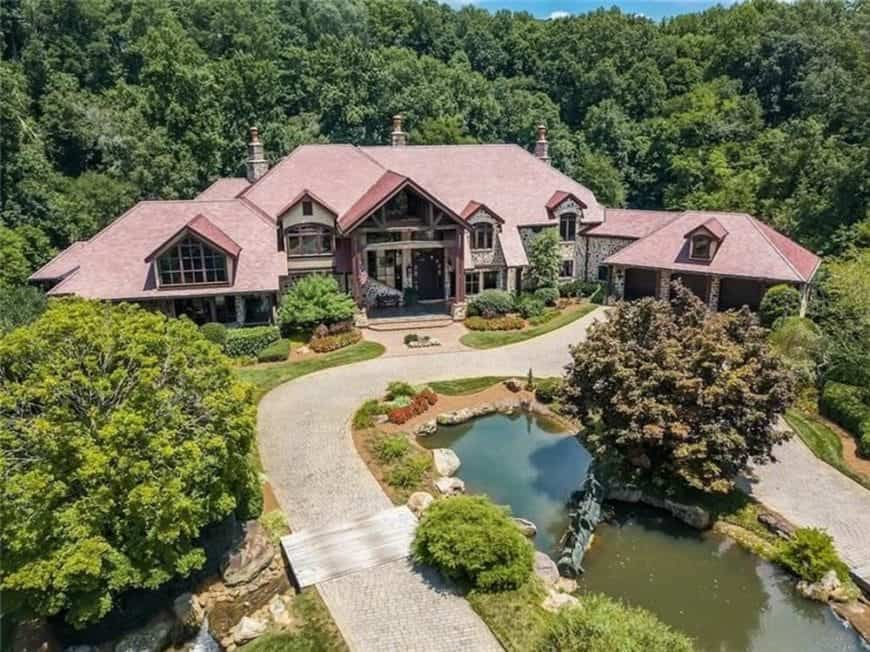 This is an aerial view of the front of the house that has earthy terracotta hues on its roof with various dormer windows and large glass walls complemented by the surrounding landscape of tall trees and shrubs.