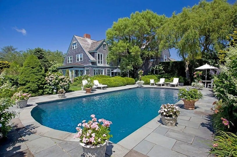 This gray house boasts a beautiful garden with healthy plants and trees. There's a swimming pool surrounded by the lovely greenery as well.