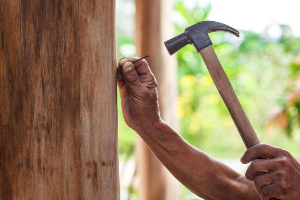 The act of pounding a piece of nail on a wooden column using a hammer.