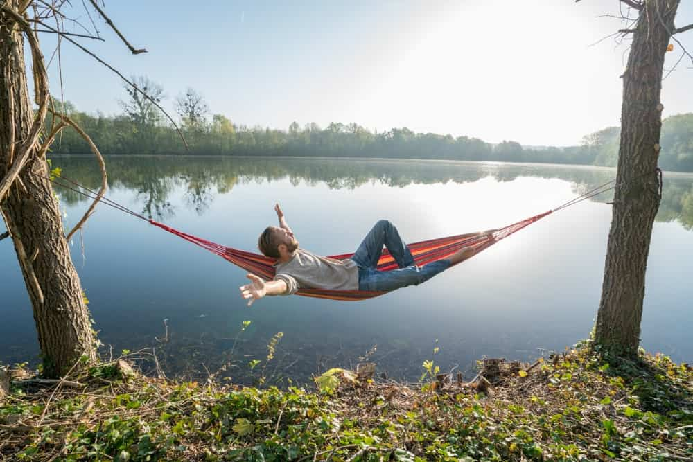 Man extends his arms out as he lies on a hammock between trees and in full view of the lake.