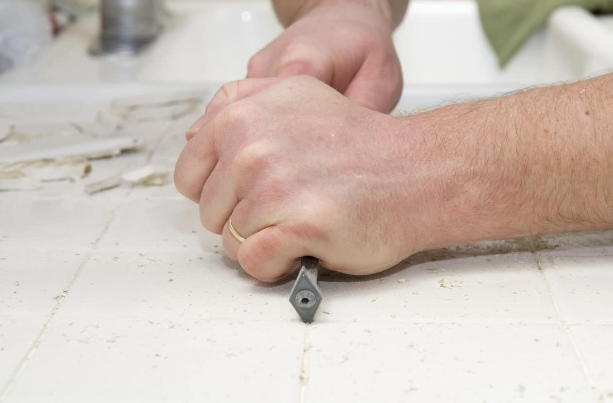 A pair of bare hands using the hand grout removal.