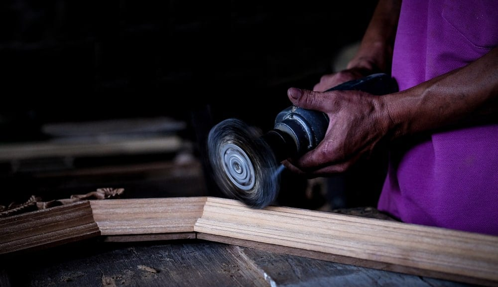 Using a handheld sander to polish the edges of a wooden surface.