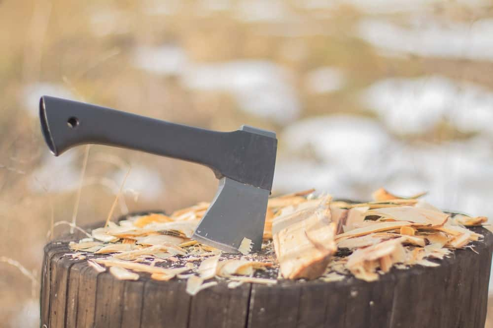 Hatchet resting on a wooden log with chips of wood on top.