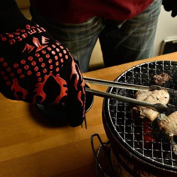 Person wearing a heat resistant gloves while grilling.