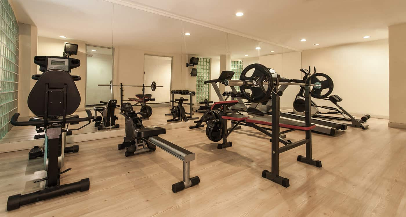 Nicely equipped home gym with a variety of cardio equipment, mirrors and wood flooring