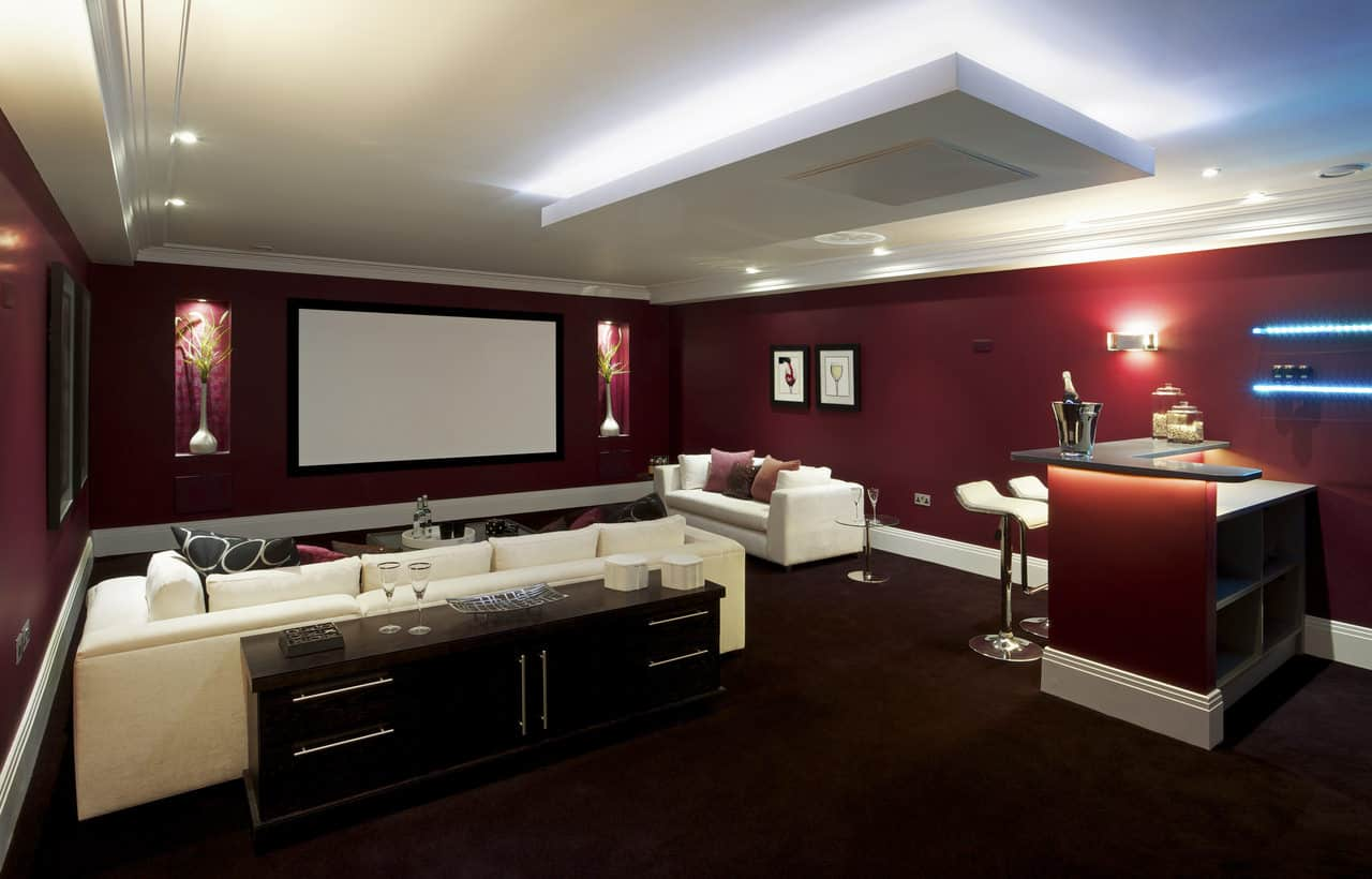 Here's an example of an elegant projector-style home theater without the stadium seating.  Instead it has two large sofas spaced out nicely.  The walls are deep red set against a white ceiling and very dark red carpeting.  There's a small built-in mini-bar at the rear.  This is a very nice room to chill out and enjoy TV, sports or movies.