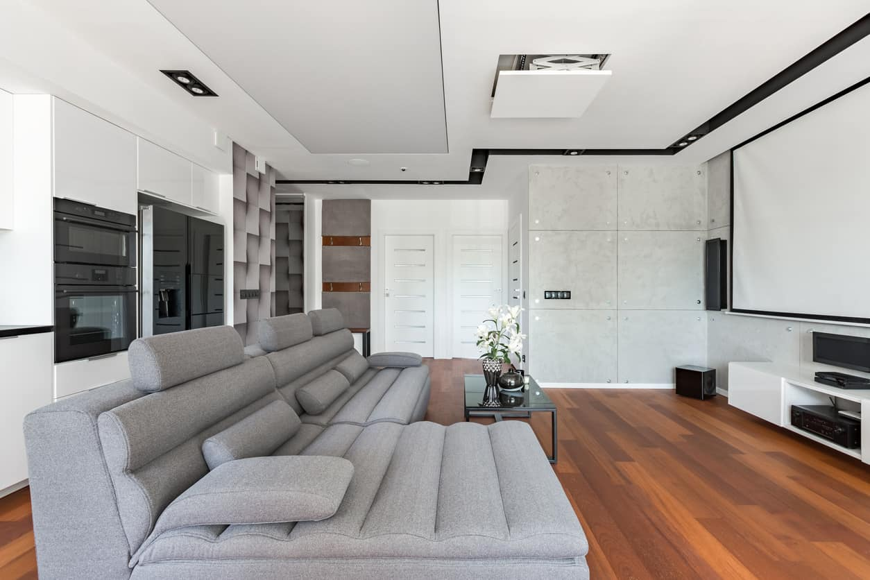 Above is a modern home media room with a sectional sofa that is both stylish and designed for watching TV.  In this case, this media room has a projector screen.  It's easy to miss, but there's a kitchen in the space as well which is really sweet... easy access to food and drinks.