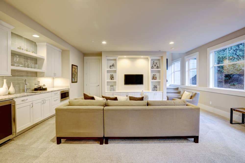 The interior designer who did this basement knocked it out of the park. Check out that very stylish yet comfortable basement family room with long wet bar spanning the side wall with custom white cabinets, wine fridge, small oven and sink. This room is totally decked out for relaxing and entertaining.