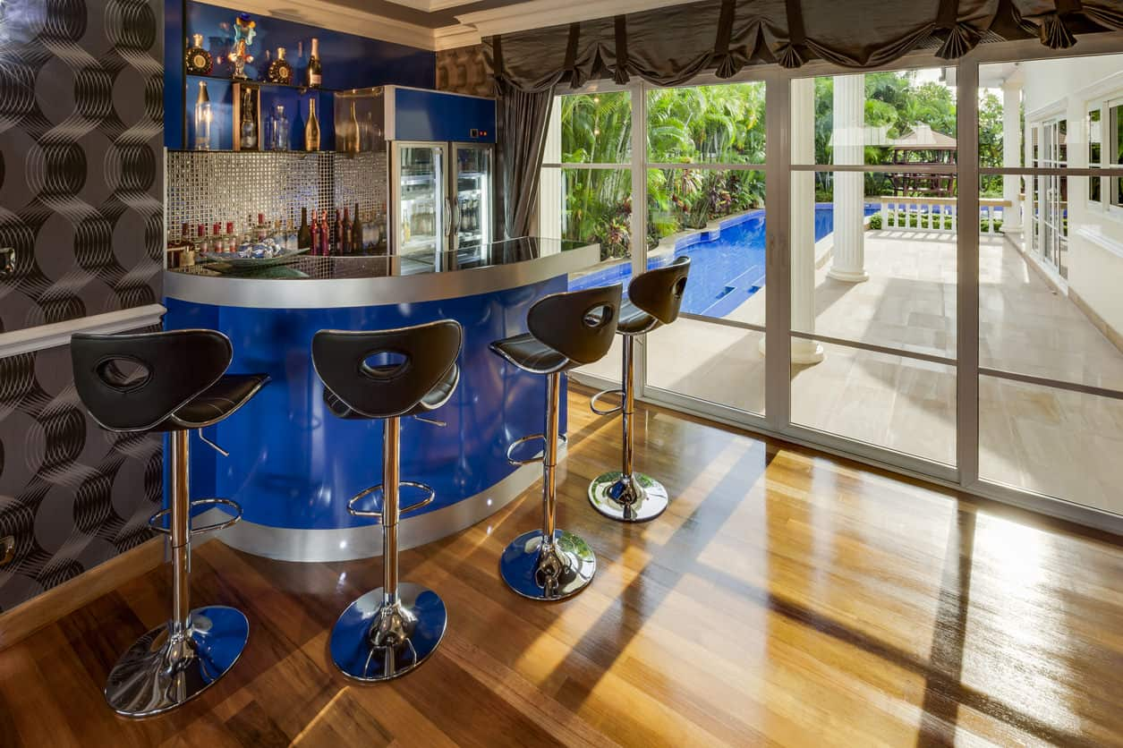 I absolutely love this home bar just inside the entrance to the covered patio and pool. While I'm usually not too much into the glam look, I like the bright blue and chrome bar design.