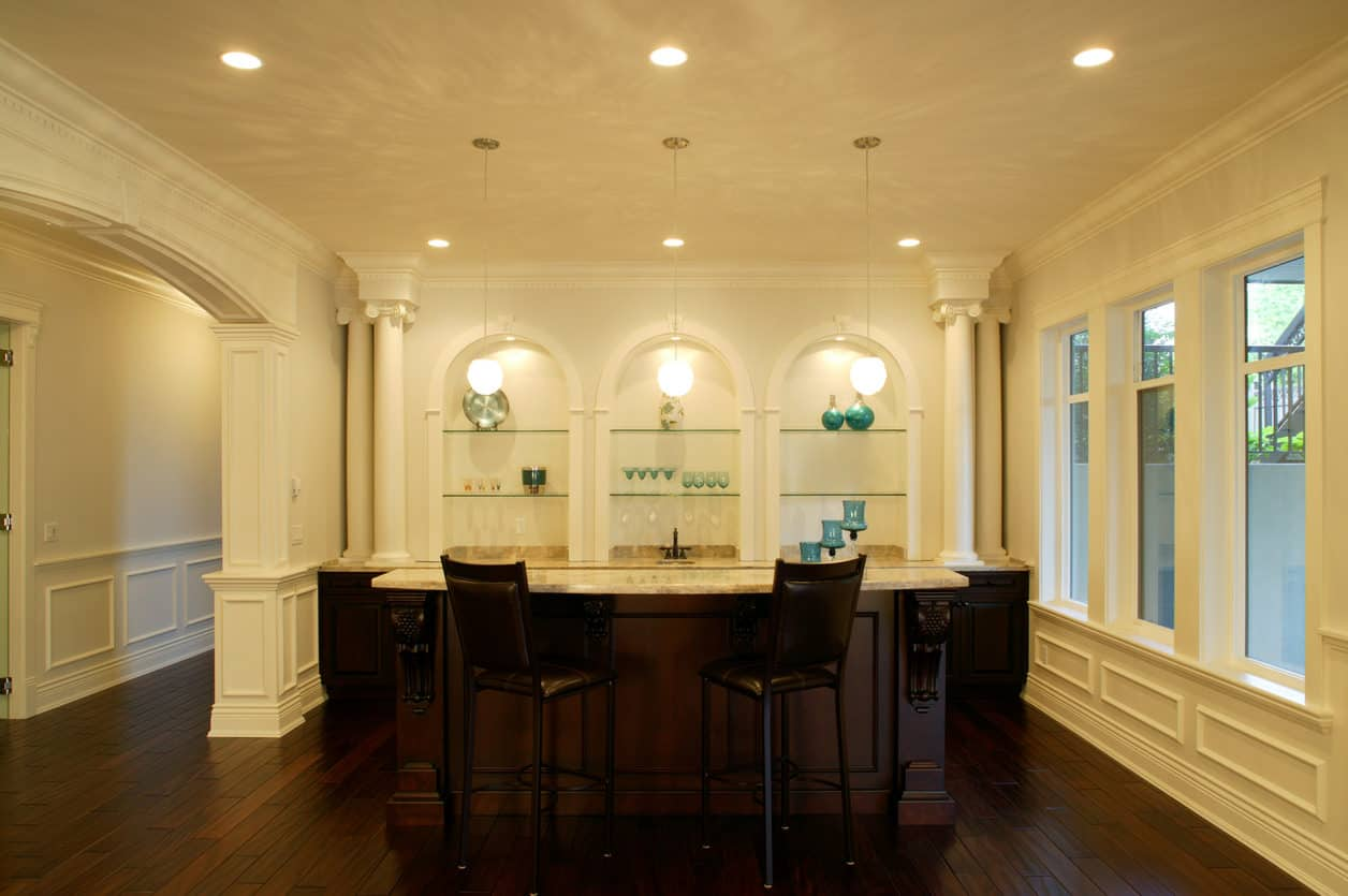 Stunning cream and dark brown luxury home bar int he basement with arched built-in shelving, columns and granite bar top with two dark brown leather upholstered stools.