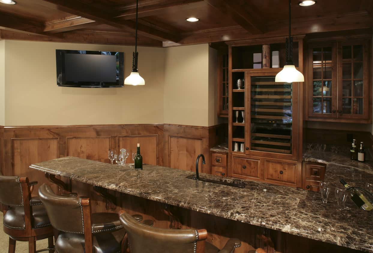 Check this saloon style home bar out. Lots of wood, granite bar surface, western style leather upholstered stools and pretty much fully stocked to serve any drink you desire.