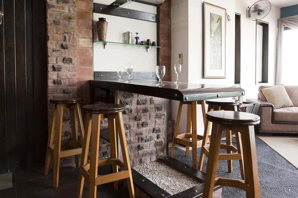 """Space-saving drop-down """"murphy-bed"""" style home bar with simple stools in a rustic style."""