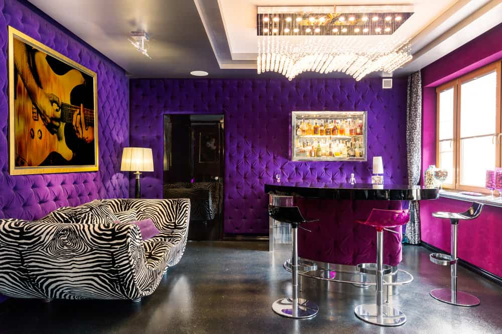 Here's a totally glammed-out home bar and lounge with purple tufted walls, fuschia and chrome stools, bring pink window wall, black floor and one super wild zebra sofa. Also, check out that incredible chandelier.