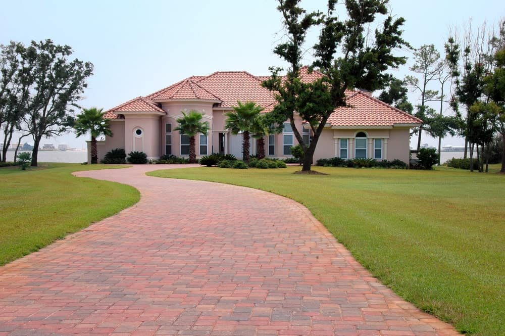 Beautiful beach house with trees on green front lawn and a spiral brick driveway that matches the house's roof.
