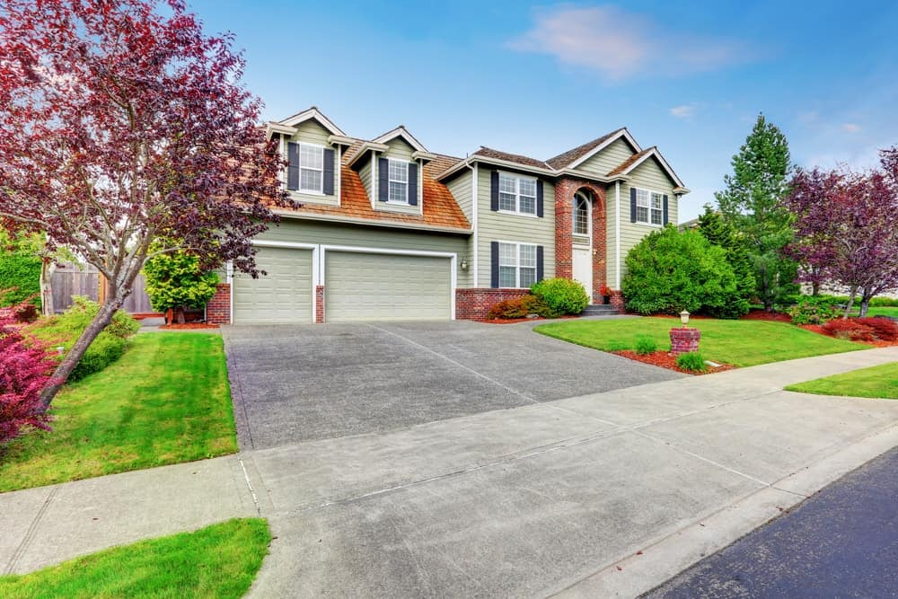 Large house with magnificent landscaping and concrete driveway.