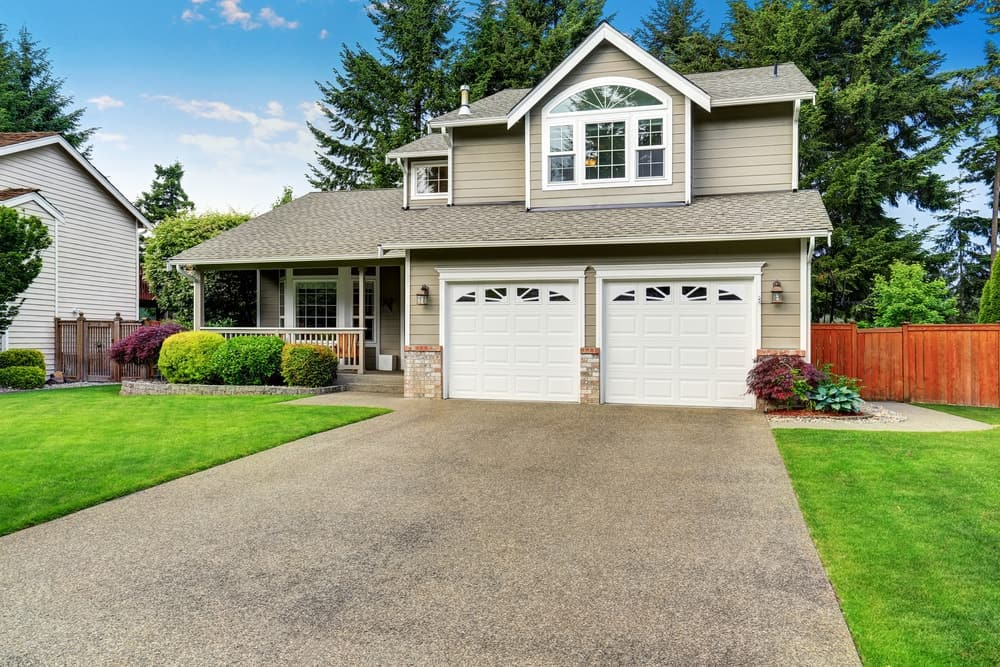 House with a porch and beautiful lawns along with a concrete driveway.