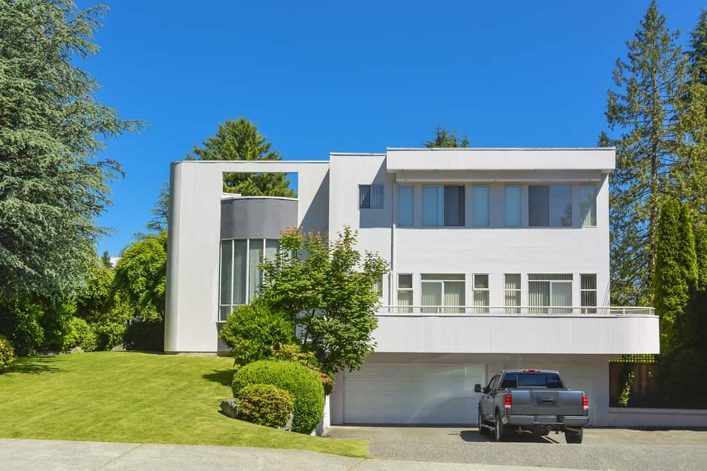 Large modern house with a nice landscaping and a concrete driveway.