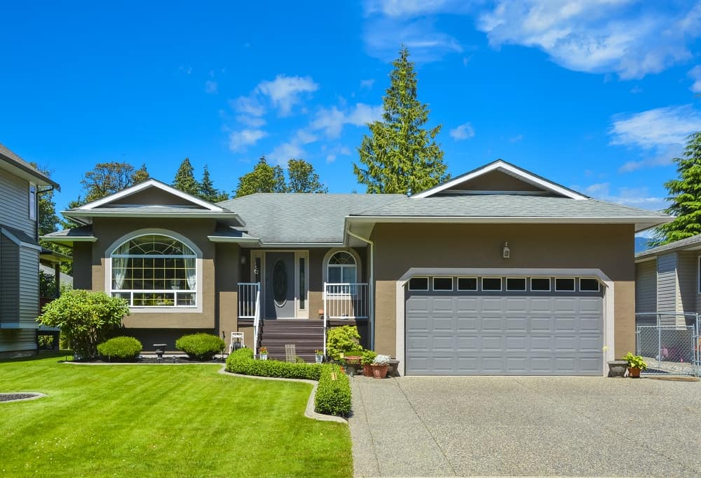 Large bungalow house with a beautiful garden area and a concrete driveway.