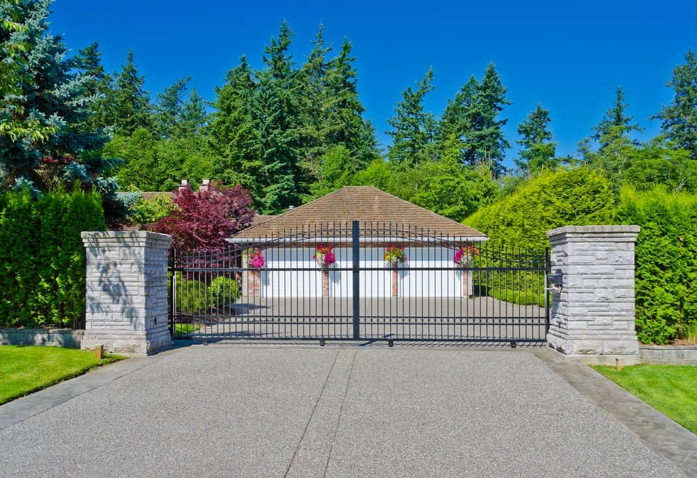 Large gated house with stunning landscaping and a concrete driveway.