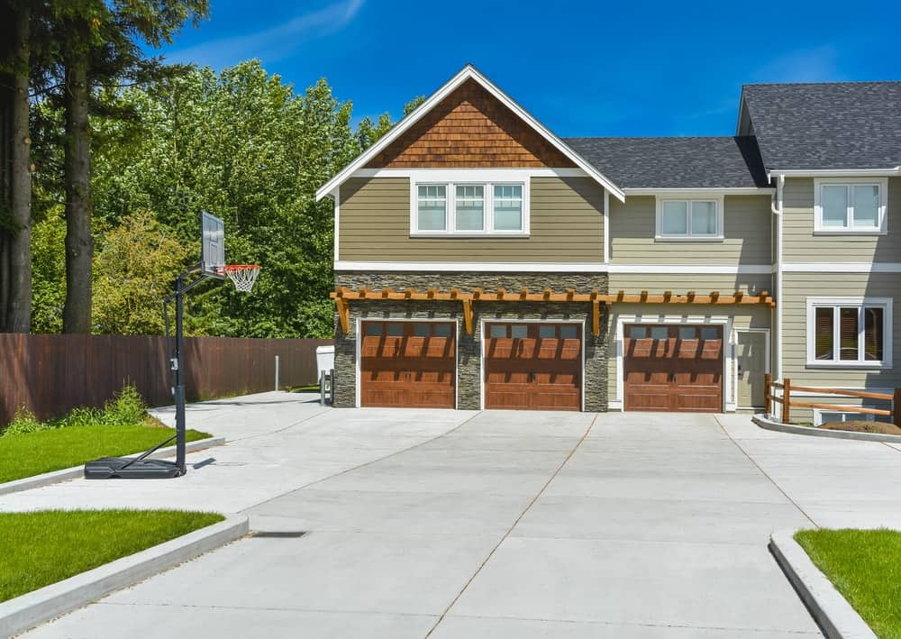 Large house with a large garage space and a basketball court near the concrete driveway.