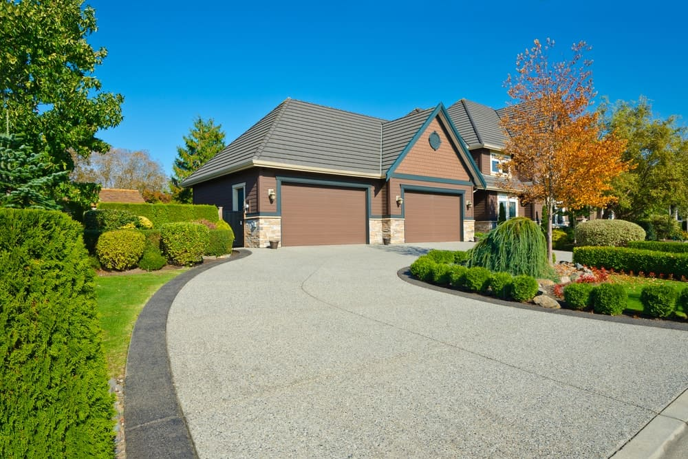 House with a large outdoor area featuring a beautiful garden and a concrete driveway.