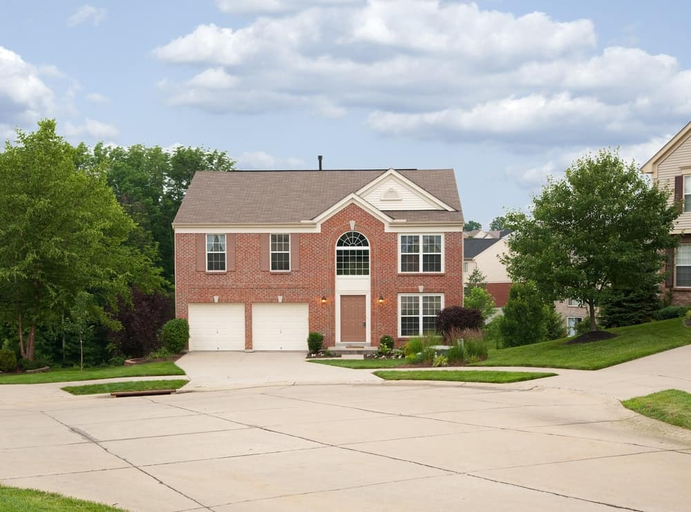 House with a beautiful landscaping and a wide concrete driveway.