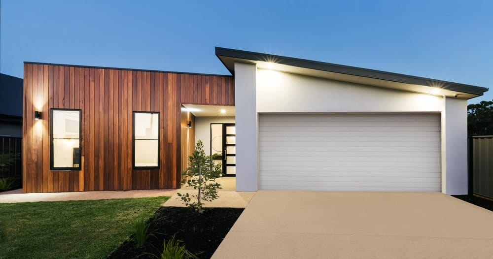 Modish house with white and wooden walls along with a concrete driveway and a lawn area.