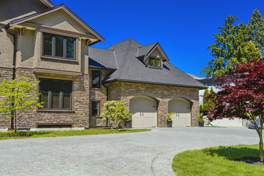 Stylish house with brick walls and beautiful trees along with a wide concrete driveway.