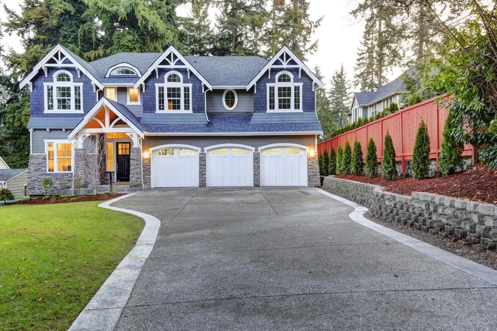 Stunning house with blue and grey exterior featuring a beautiful lawn area and concrete driveway.