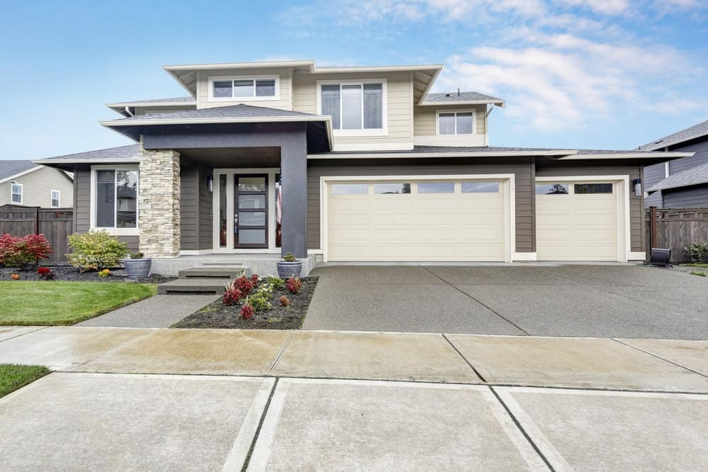 White and grey exterior house with small garden area and a concrete driveway.