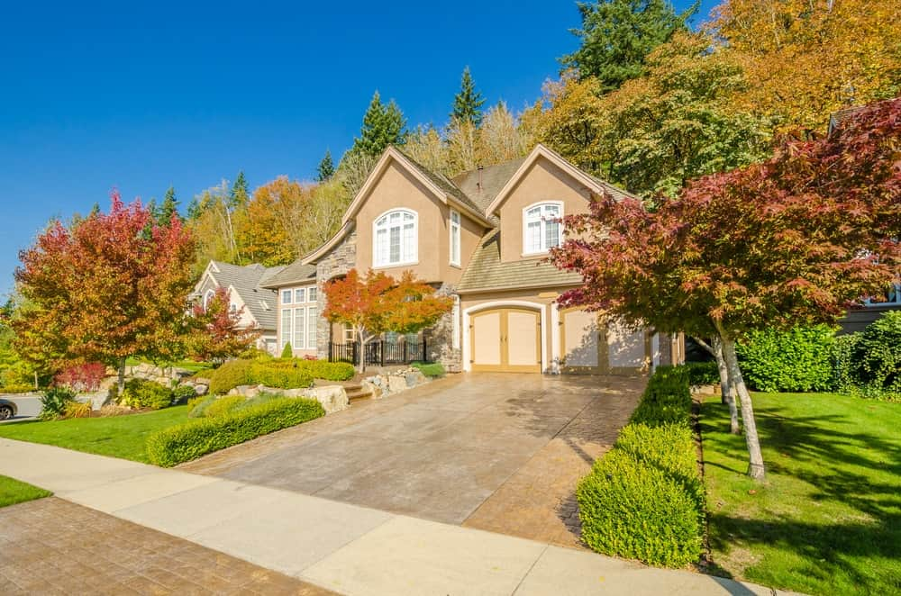 House with a colorful surrounding trees and a beautiful garden area along with a concrete driveway.