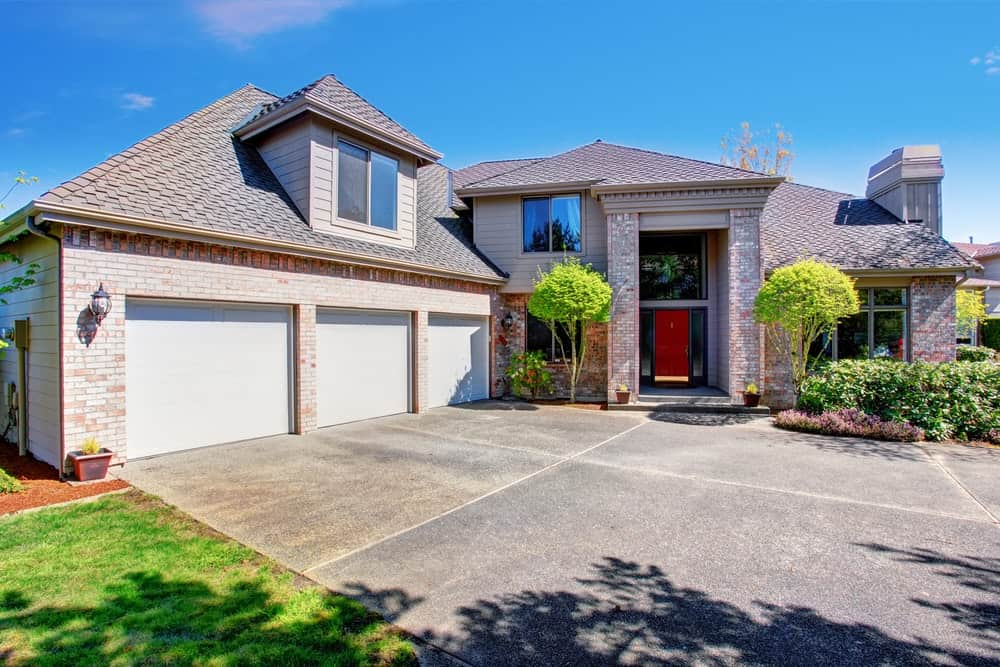 Large modish house with a large concrete driveway and beautiful garden area.
