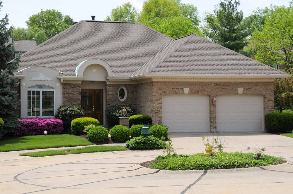 House with brick-style walls featuring beautiful garden area and a large concrete driveway.