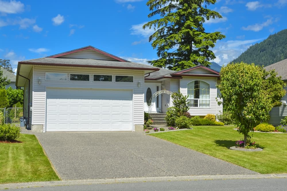 House with white exterior featuring beautiful garden area and a short concrete driveway.