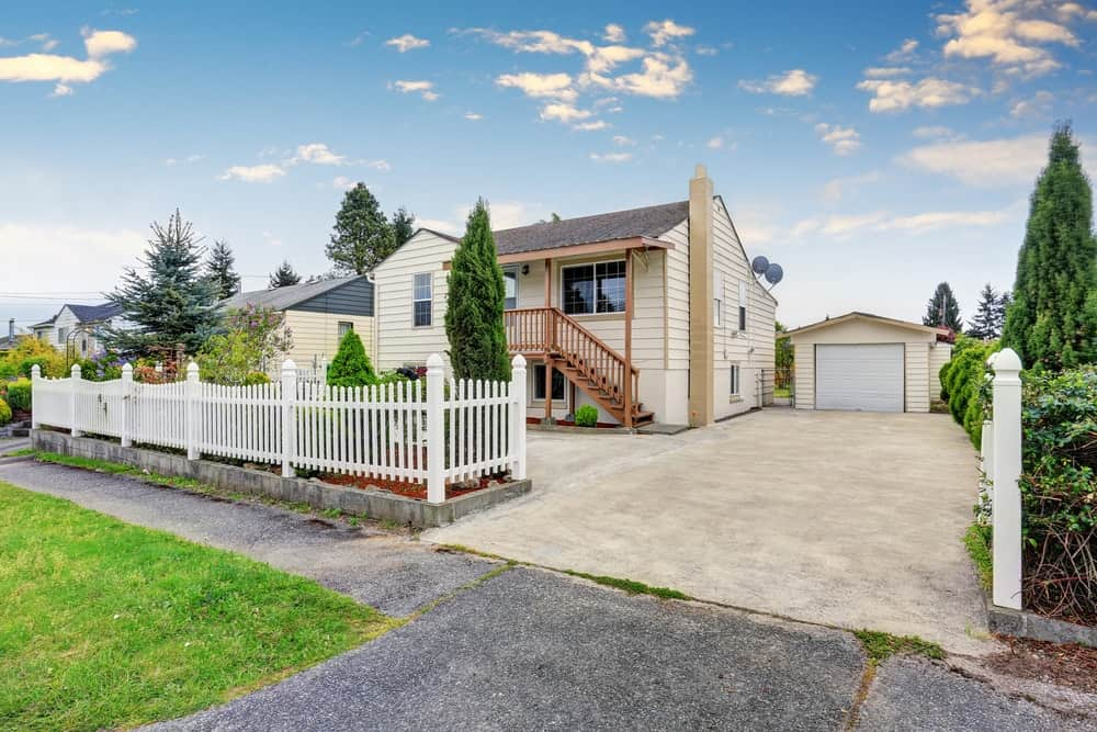 House with white exterior and white fence featuring a concrete driveway.