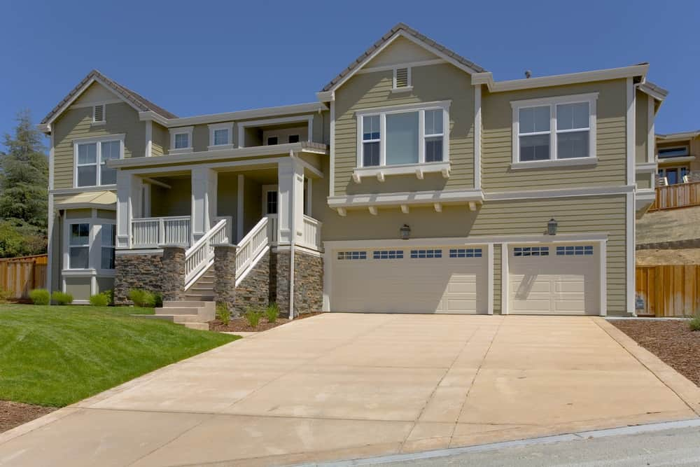 Large house with a wide concrete driveway and a garden area on the side.