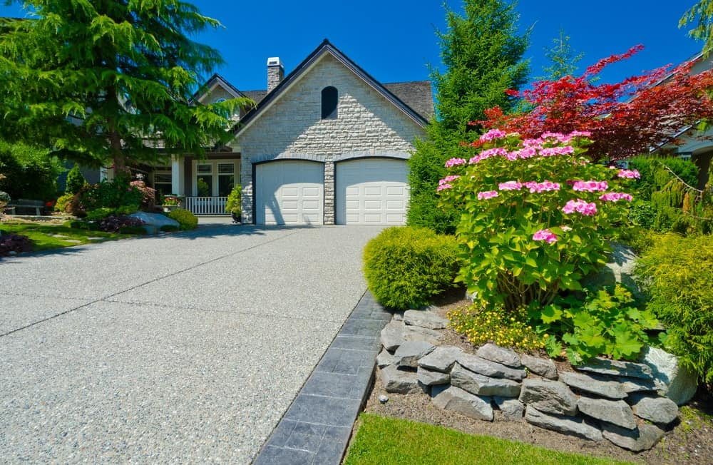 House with adorable garden and a concrete driveway.