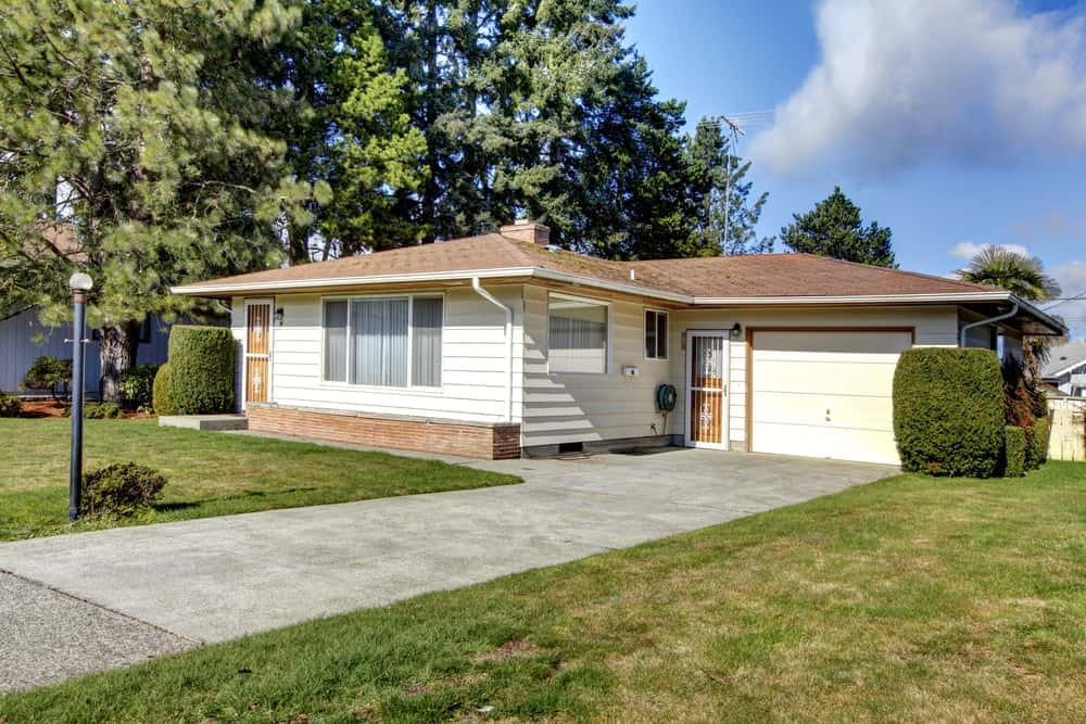 Bungalow-style house with charming landscaping and a concrete driveway.