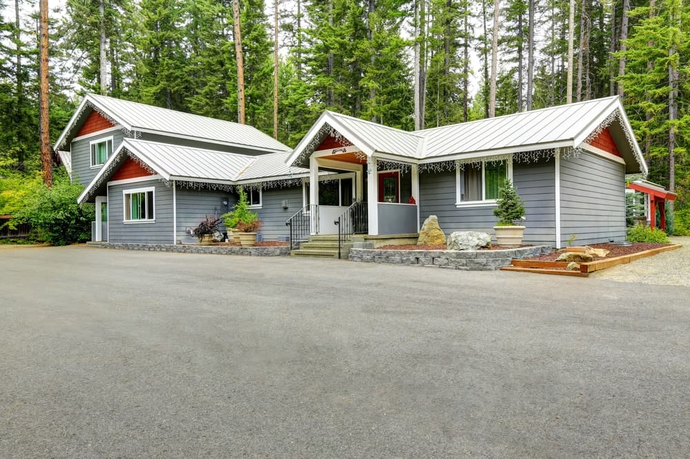Bungalow-style house with grey exterior featuring stunning landscaping and a wide concrete driveway.