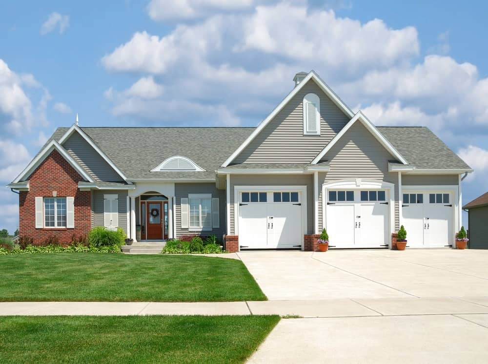 Bungalow-style house with grey exterior and beautiful greenery along with a concrete driveway.