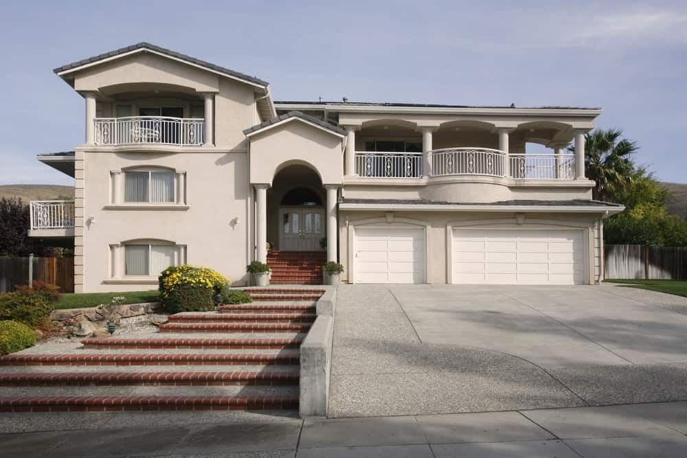 House with a terrace and an elegant walkway with a concrete driveway on the side.