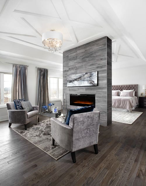Transitional primary bedroom with wood flooring, fireplace separator wall and white cathedral ceiling.