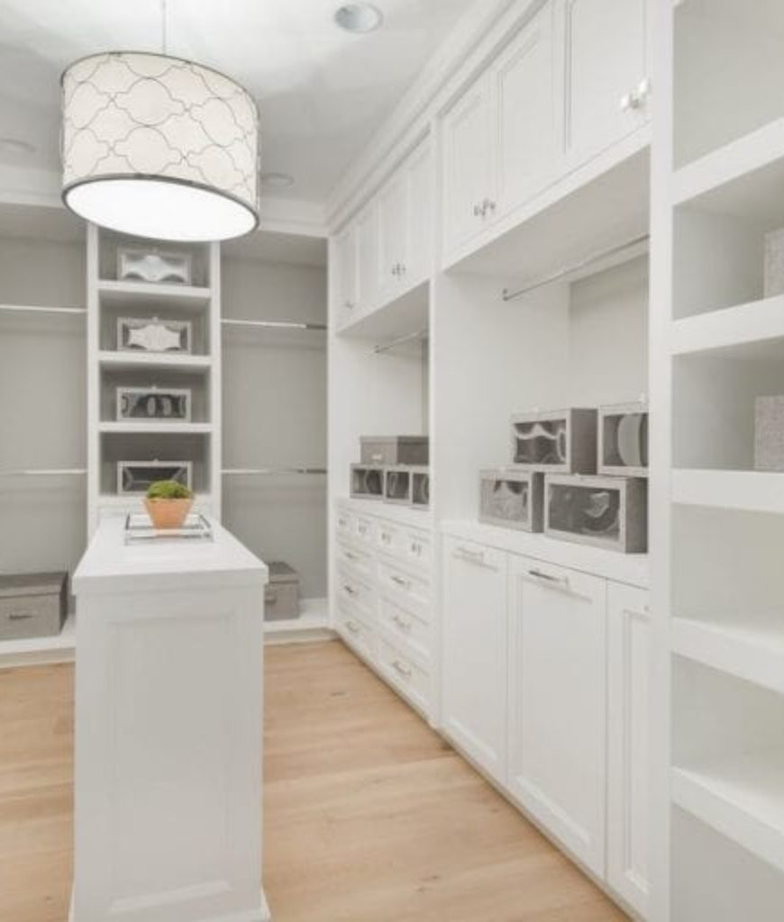 The closet features white cabinetry and flushmount light along with a center island.