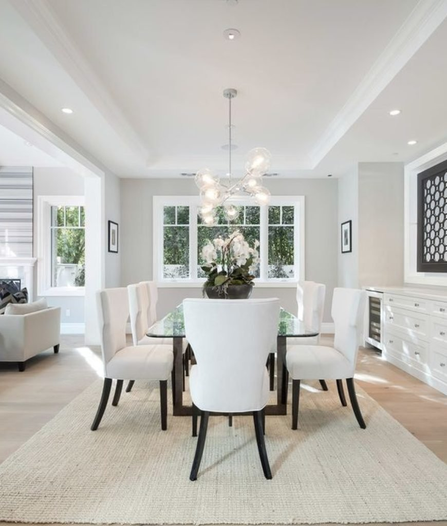 The dining room features classy table and chairs set along with a rug and ceiling light.