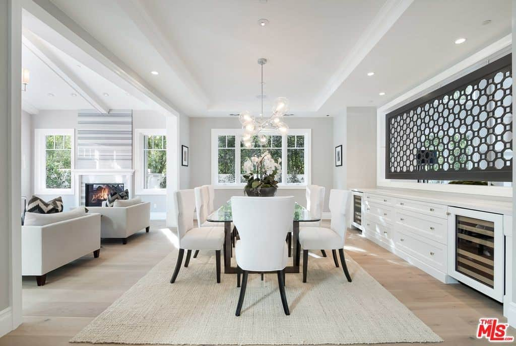 Formal dining room features a white built-in buffet table beneath a decorative perforated metal panel. It has a glass dining table surrounded with white chairs and accented with a statement chandelier.