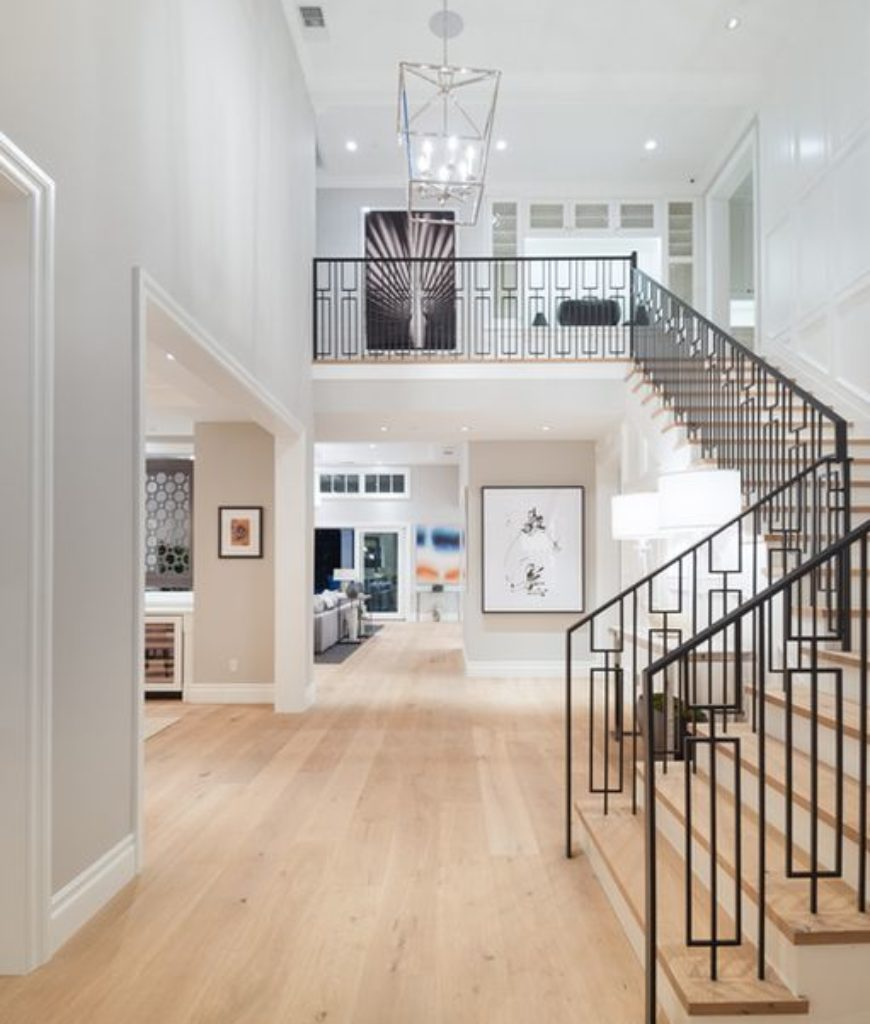 The entry features high ceiling and three quarter turn staircase along with hardwood flooring.