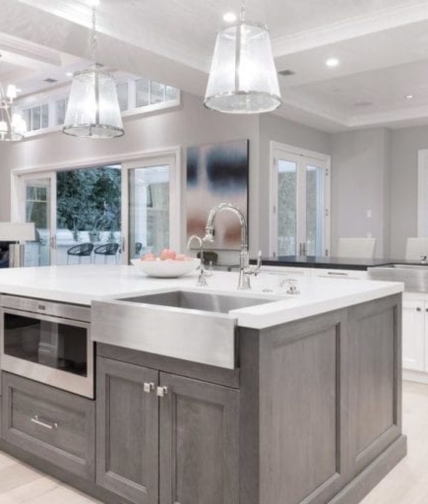 The kitchen features a large center island and bright ceiling lights along with smooth white countertops.