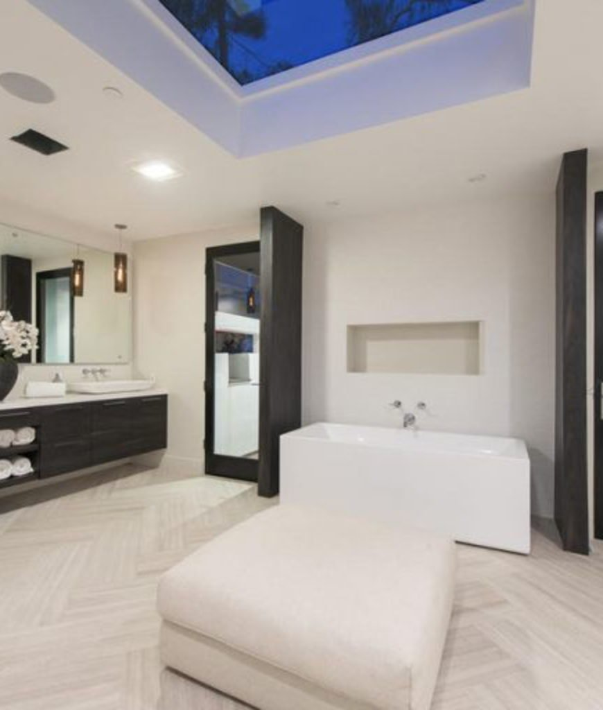 The bathroom features a wide space with a seat on the center. The room is also complete with a soaking tub, sink and a shower room.