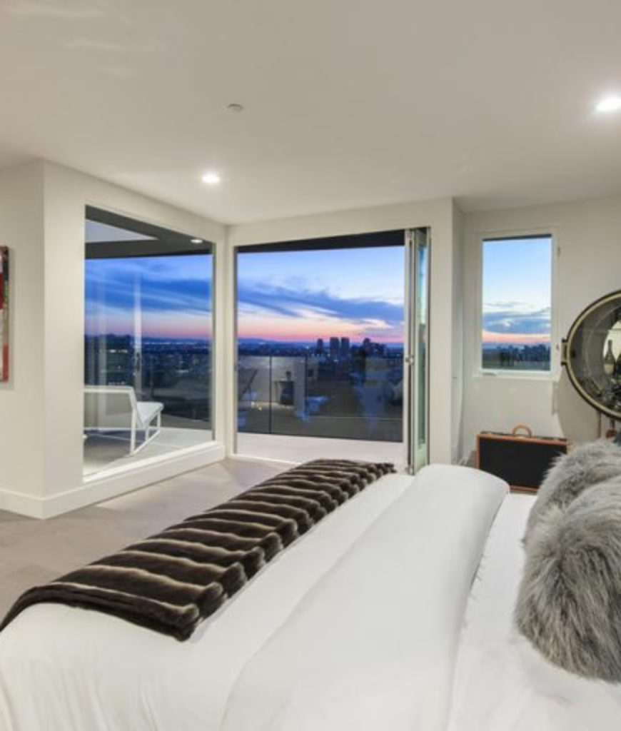 Another view at the master bedroom showcasing its large bed and doorway leading to the private balcony.