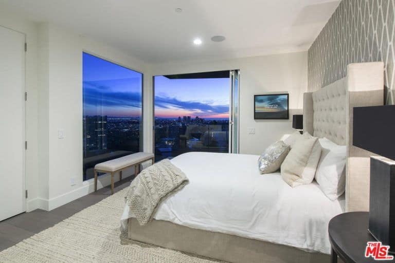 Another bedroom features a large bed and windows overlooking the city of LA.